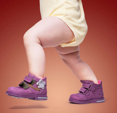 Foto per the stylish baby goes in boots. on a color backgroun - Immagine Royalty Free