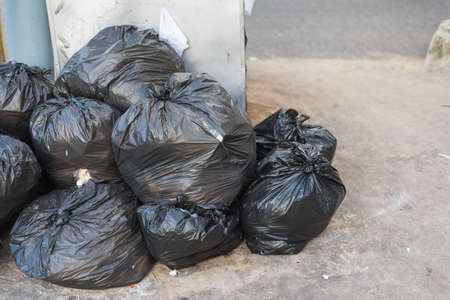 image of black garbage bag on the street.
