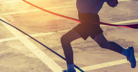 Foto de Silhouette image of ribbon at finish line with kids winner crossing it.(focus on ribbon) - Imagen libre de derechos