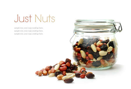 Studio macro of mixed nuts and dried fruit in a jar next to a heap of nuts on a white background with soft shadows