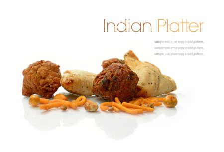 Studio macro of delicious Indian snacks, vegetable samosas, vegetable pakoras and onion bhajis on a white background. Copy space.