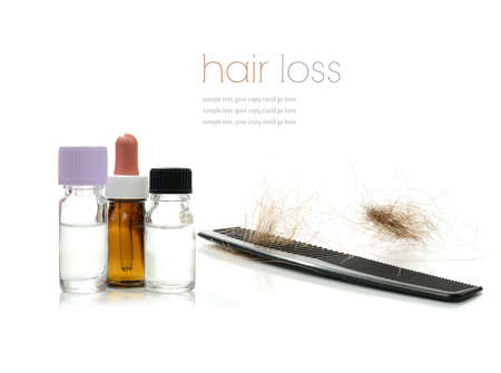 Concept image depicting alternative treatments for hair loss with medication bottles and comb against a white background  Copy space