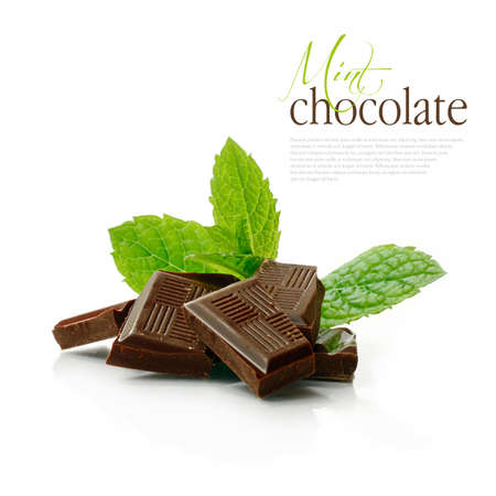 Studio macro of dark chocolate pieces with fresh green mint leaves on a white surface. Copy space.