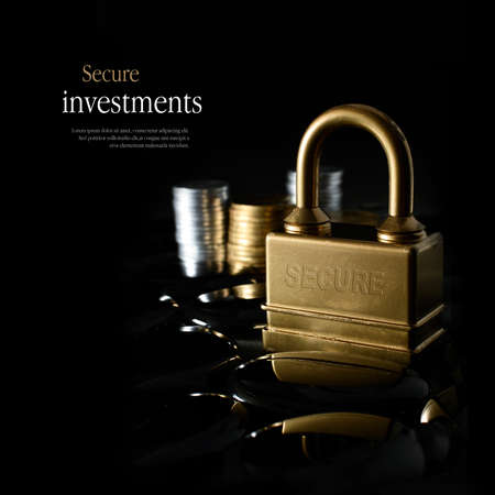 Concept image for secure financial planning. Creatively lit, stacked generic gold and silver coins representing client investment or savings with a gold padlock representing security. Copy space.
