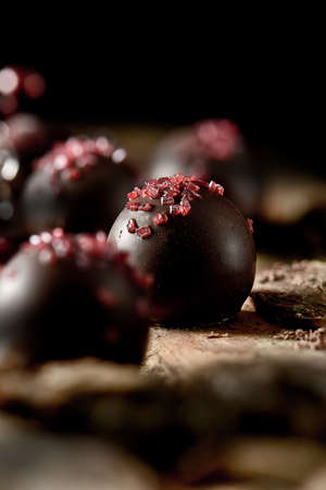 Photo pour Dark, autumnal, rustic styled dark Belgium Liqueur Chocolates with gelatin chip sprinkles shot with directional light and selective focus against black. Accommodation for copy space. - image libre de droit