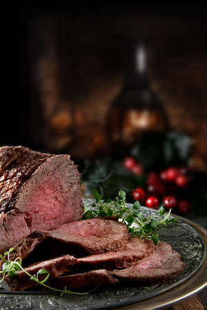 Foto per Succulent prime roast beef topside rump joint carved and ready for serving. Shot against a rustic, festive background with generous accommodation for copy space. - Immagine Royalty Free