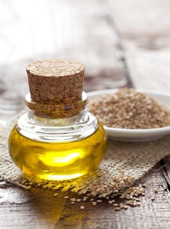 sesame oil and sesame seeds on table