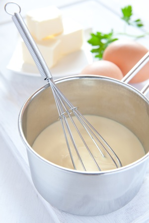 preparing hollandaise sauce in a pot with ingredients