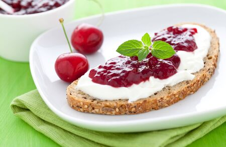 fresh bread with jam with cherries on a plate