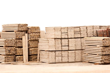 Photo pour Pile of wooden planks in gravel ground against white wall - image libre de droit