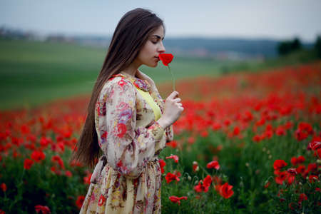 Photo for A young woman with long brown-haired wearing in floral dress, standing with back in the red poppies flowers field, smells poppy, on beautiful summer landscape background. Horizontal view. - Royalty Free Image