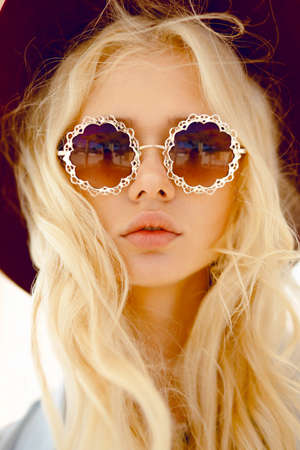 Photo for Beauty portrait of a cute blonde haired with round floral eyeglasses, big lips,wavy hair and burgundy hat, looking sensual at camera. Vertical view - Royalty Free Image