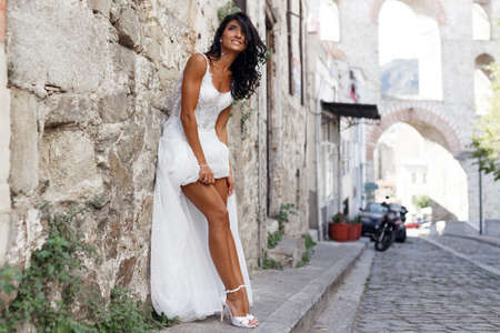 Foto de Gorgeous bride in a sexy white dress near old greece city, showing his sensual legs, poses near white stone wall in street in summer time. Travel, wedding abroad. Copy space. - Imagen libre de derechos