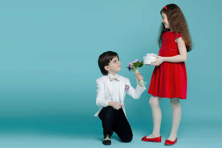 Photo for Portrait of a two adorable brunette boy in a eyeglasses and curly girl, in white suit and red dress, posing in romantic poses on a blue background, with copy space. - Royalty Free Image