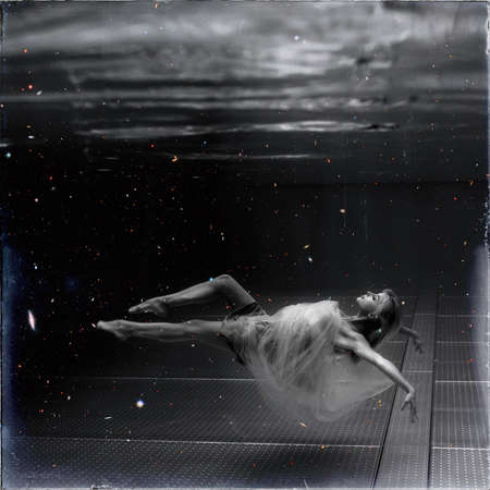 Photo for Black and white image. Underwater photo beautiful blonde wearing in white flying dress, swimming in pool underwater. - Royalty Free Image