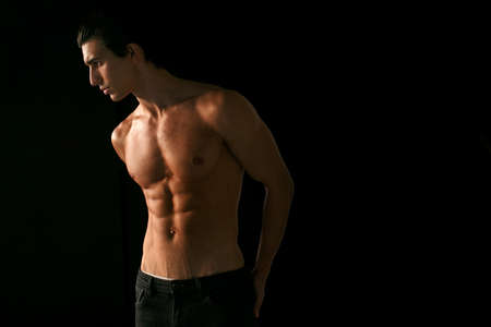 Foto für Profile portrait of a young man with shirtless torso with tanned skin, over black background. Space for text. - Lizenzfreies Bild