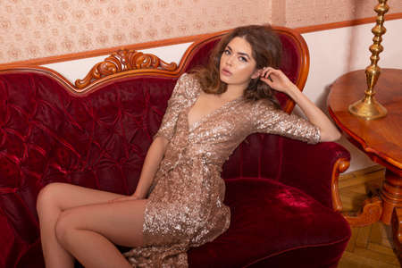 Foto de Young beautiful woman in gold sequin dress. fashion model posing on sofe. Curly brunette hairstyle for glamour lady. - Imagen libre de derechos