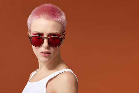 Photo pour Nonconformist young woman magenta short hairs pink with red sunglasses, over brown background. Space for text. - image libre de droit