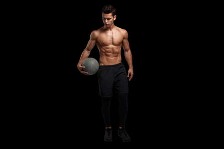 Photo for Portrait of a handsome brunette young man with muscular body holding a bascket ball, posing at studio. Black background. - Royalty Free Image