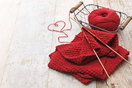 Foto de hand knitted red scarf and heart shaped thread - Imagen libre de derechos