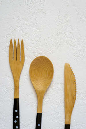 Bamboo fork, knife and spoon on white background closeup, Top view with copy space