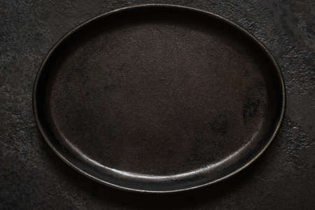 Empty rustic black cast iron plate On Dark concrete background. Top view with copy space.