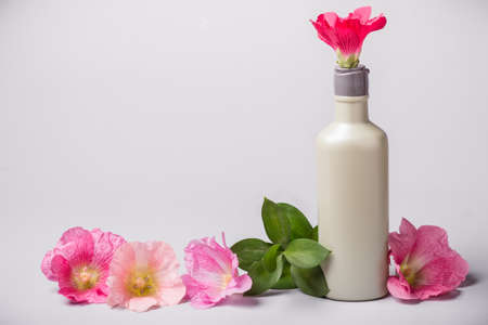 Bottle with cosmetic product and mallow flowers. Natural Ecology concept. Toned.