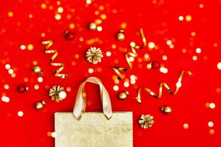 Photo pour Golden Paper shopping bag, cones and sparkles lights on red - image libre de droit
