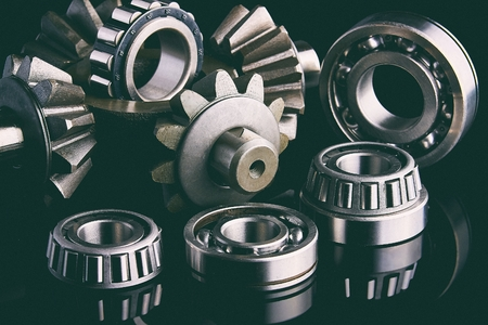 Photo pour Gears, bearings and differential are on the table in the dark. Can be used as a background. - image libre de droit