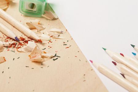 Pencils with color shaving and  sketchpad on wooden table