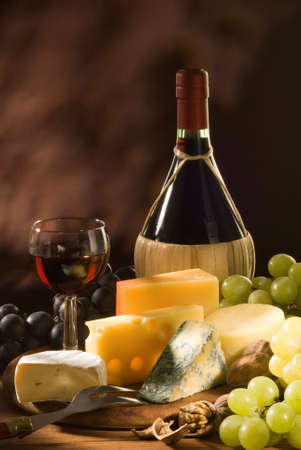 Glass and bottle of red italian wine with various types of cheese and garnishes