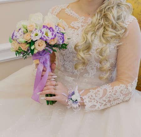 Foto de Young happy bride holding a wedding bouquet in her hands. - Imagen libre de derechos