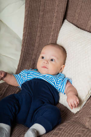 Photo for Beautiful little boy on a chair with a plaid. - Royalty Free Image