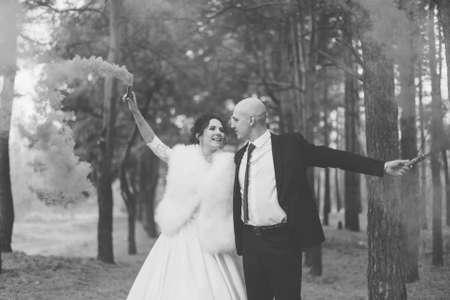 Foto für Happy bride and groom hold colored smoke in their hands. - Lizenzfreies Bild
