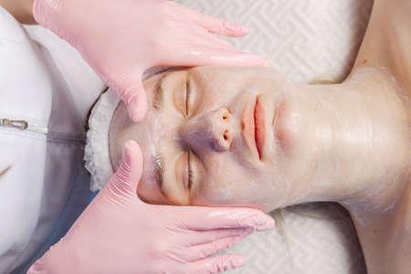 Photo pour Professional beautician makes a facial massage to a woman. - image libre de droit