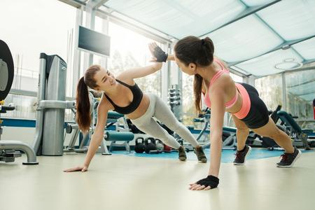 Foto de Young attractive slim friends in sportswear doing press ups exercises and giving high five in modern gym - Imagen libre de derechos