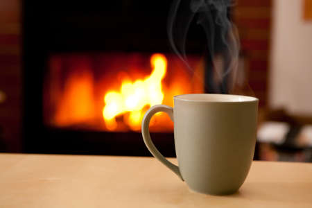 A coffee cup filled with a steaming liquid in front of a fireplace