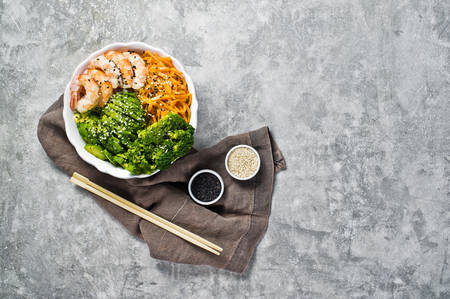 Foto de Buddha bowl with shrimps, avocado, carrot, brocoli and rice. Balanced food. Gray background, top view, space for text - Imagen libre de derechos