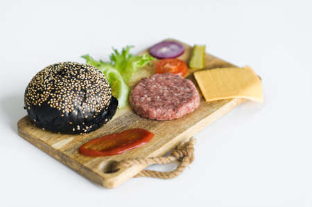 Ingredients for the black Burger on wooden cutting Board