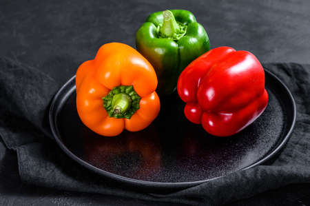 Photo pour Green, orange and red bell peppers on a plate. Black background. Top view. - image libre de droit
