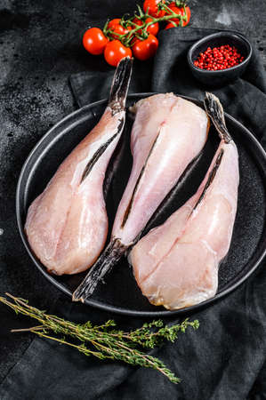 Photo pour Separate fresh monkfish without head and skin. Black background. Top view. - image libre de droit