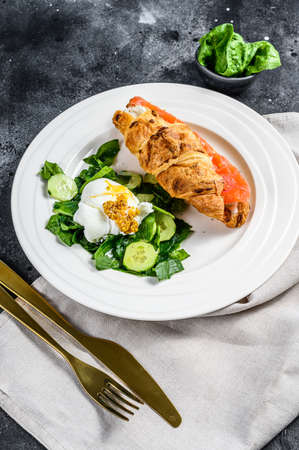Photo pour Croissant sandwich with salted salmon served with fresh salad leaves spinach, egg and vegetables. - image libre de droit