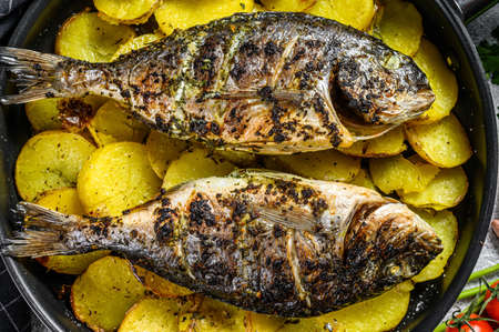 Photo pour Grilled Dorado fish with potatoes in a pan. Gray background. top view. - image libre de droit