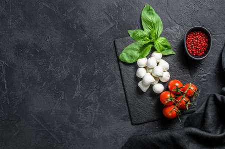 Photo for Mini mozzarella cheese, Basil leaves and cherry tomatoes, cooking Caprese salad. black background. top view. Copy space. - Royalty Free Image