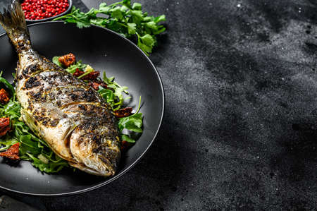 Photo pour Baked sea bream fish with arugula salad and tomatoes. Black background. top view. Copy space. - image libre de droit