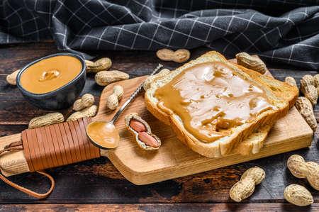 Foto de Crispy toast with peanut butter on breakfast. Dark Wooden background. Top view. - Imagen libre de derechos