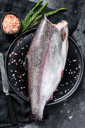 Photo for Fresh trout fish with salt and rosemary. Black background. Top view. - Royalty Free Image