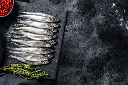 Photo for Raw small fish anchovies with pepper and thyme. Black background. Top view. Copy space. - Royalty Free Image