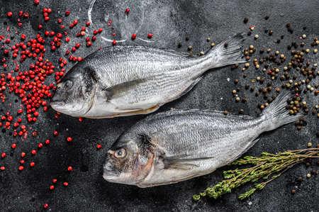 Photo pour Sea bream fish. Mediterranean cuisine, healthy cooking concept. black background. top view. - image libre de droit