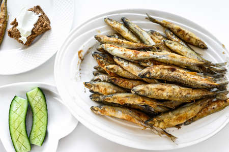 Photo pour Appetizer of fried sprat and vegetables. White background. Top view. - image libre de droit